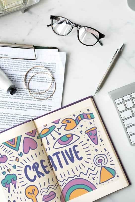 creative story book near black framed eyeglasses