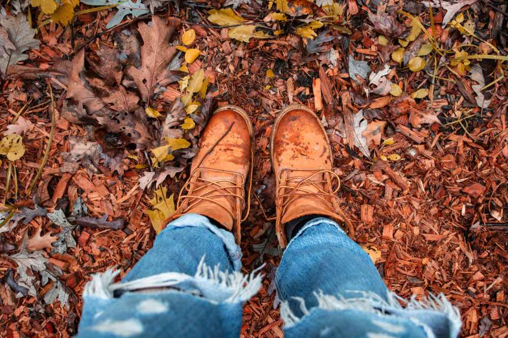 person wearing distressed blue denim jeans and brown leather boots standing